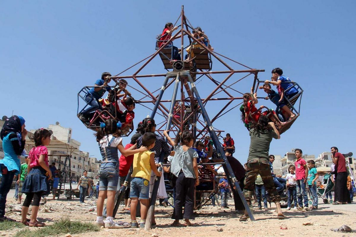 Syrian children ride on an attraction as they celebrate Eid al-Fitr on July 6, 2016.