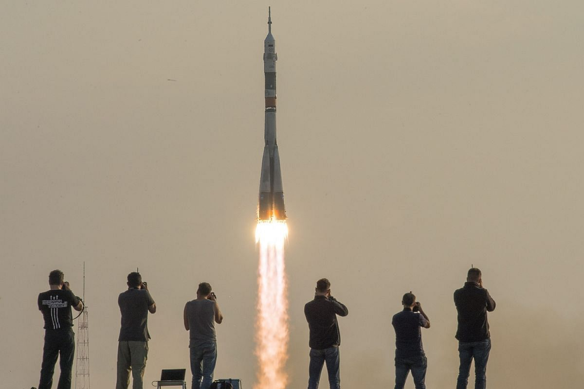 A line of photographers standing before the Soyuz MS-01 spacecraft's launching from the Baikonur Cosmodrome in Kazakhstan on July 7.