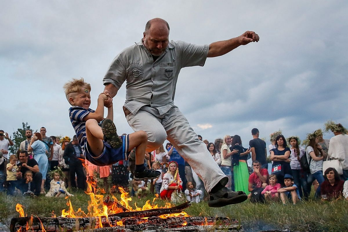 A man with a young boy jumps over a fire during the traditional Slavic celebrations of Ivana Kupala in Kiev, Ukraine, on July 6.