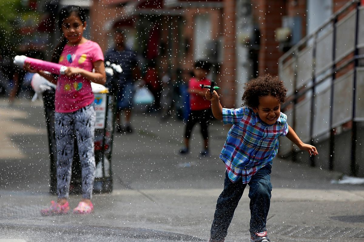 Children run through water spraying from a fire hydrant in the Queens borough of New York on July 6.