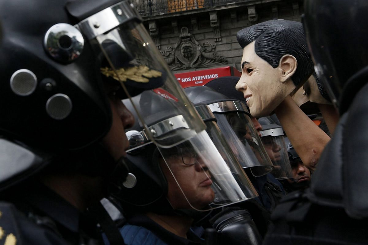 A member of the National Coordinator of Workers of Education of Mexico holds a mask resembling Mexican President Enrique Pena Nieto during a protest against the education reform in Mexico City, Mexico, on July 5.