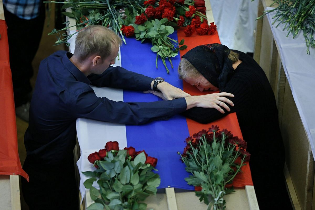 Relatives mourn during a funeral ceremony for the crew of a firefighting plane in the town of Zhukovsky outside Moscow, Russia, on July 6.