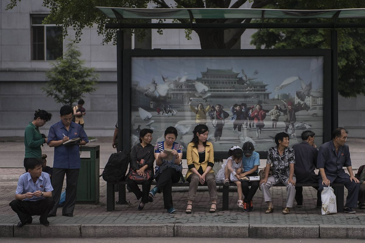 Commuters wait at a bus stop in central Pyongyang, North Korea, on July 7.