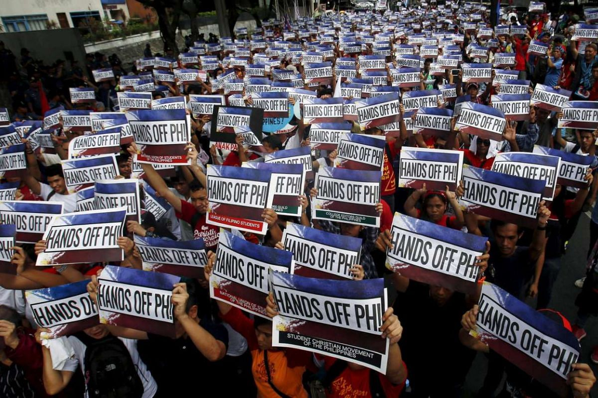 Activists hold up signs during a protest over the South China Sea disputes outside the Chinese Consulate in Makati City, Metro Manila on June 12, 2015.