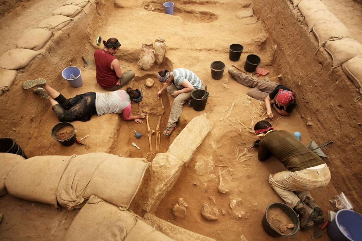 Archaeologists working at an excavation site at the Philistine cemetery in Ashkelon National Park, on June 28, 2016.