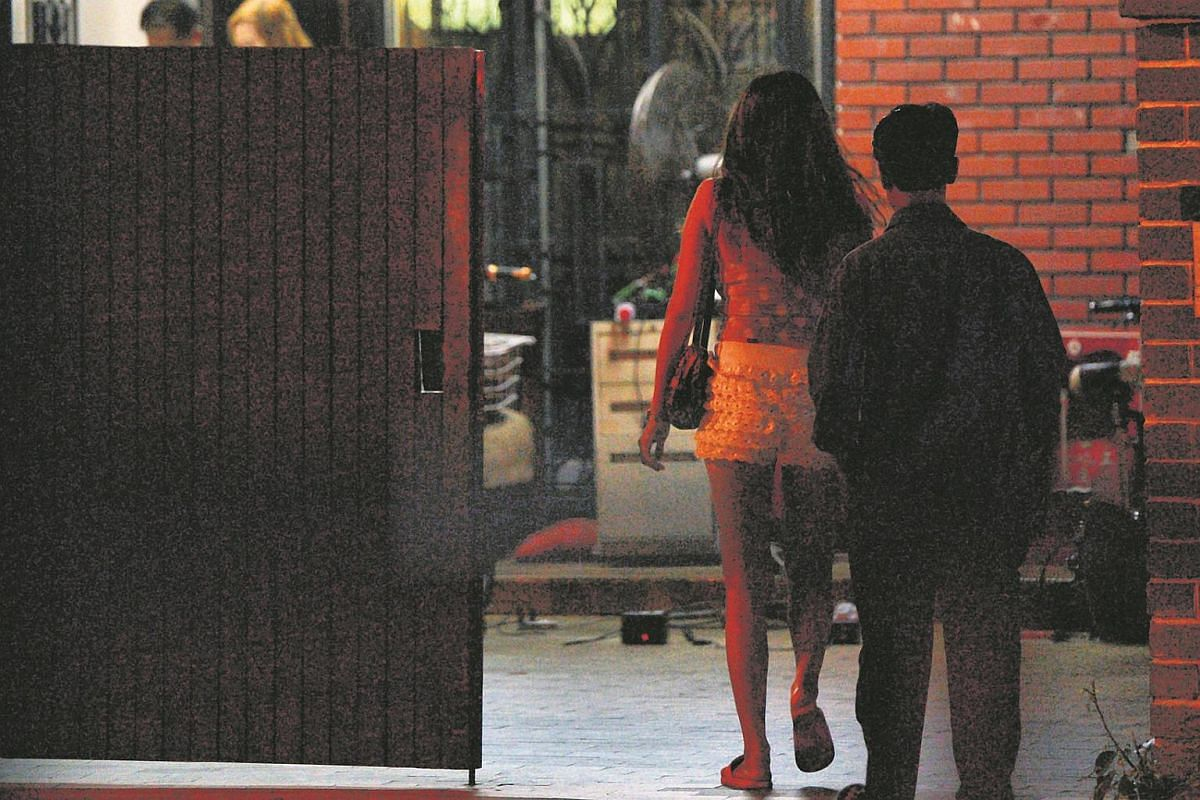A street walker and her customer seen entering a house that offer transit hourly rates along Lorong 18 Geylang.