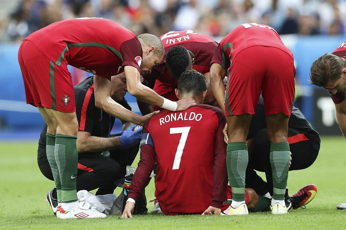 Teammates talk to Cristiano Ronaldo as he sits injured on the pitch during the Euro 2016.