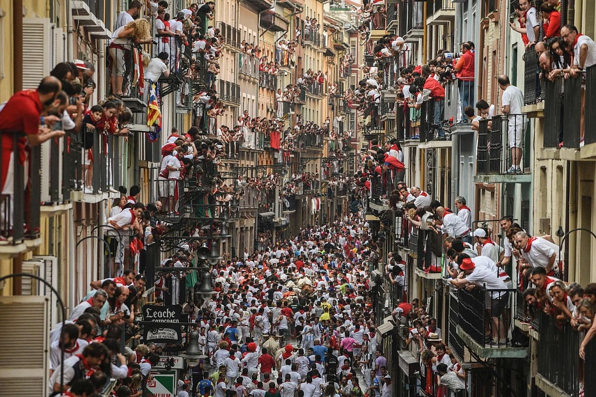 Participants run ahead of Pedraza de Yeltes' fighting bulls on the fourth day of the San Fermin bull run festival in Pamplona, northern Spain, on July 10.