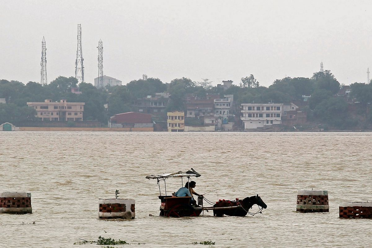 People travel on a horse-drawn carriage through a flooded road on the banks of river Ganga in Allahabad, India, on July 10.