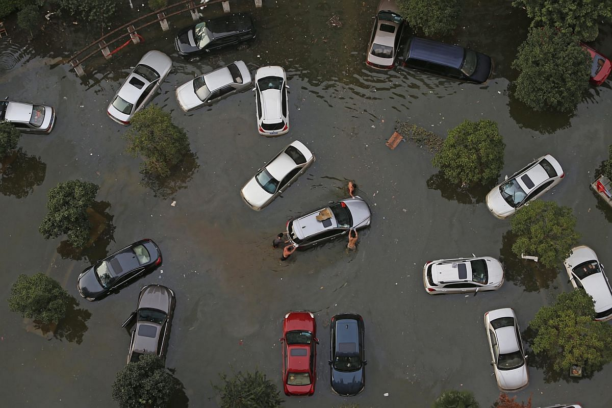 People pushing a car after flood waters receded to reveal the submerged vehicles in Wuhan, Hubei Province, China, on July 9.