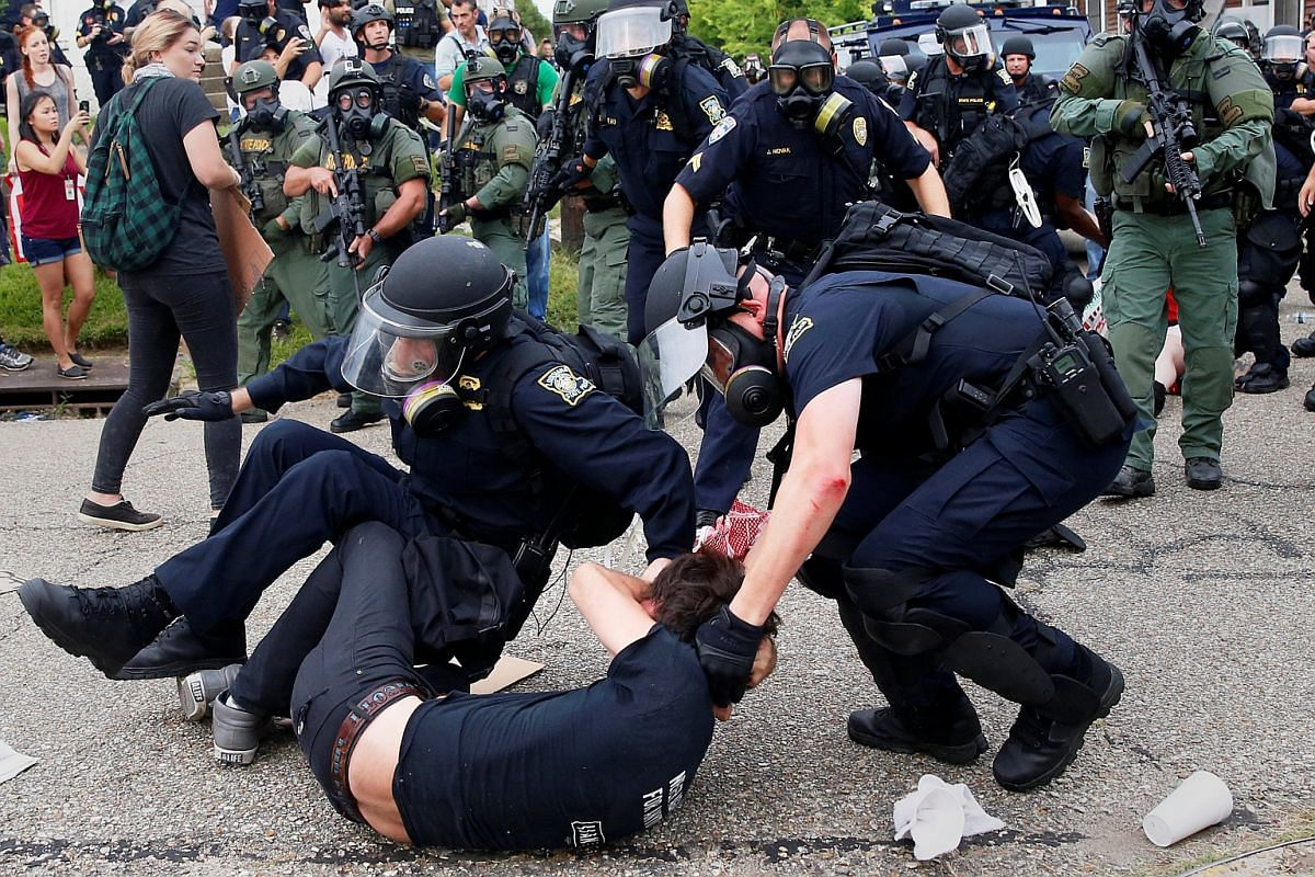 A demonstrator is detained by police during protests in Baton Rouge, Louisiana, US, on July 10.