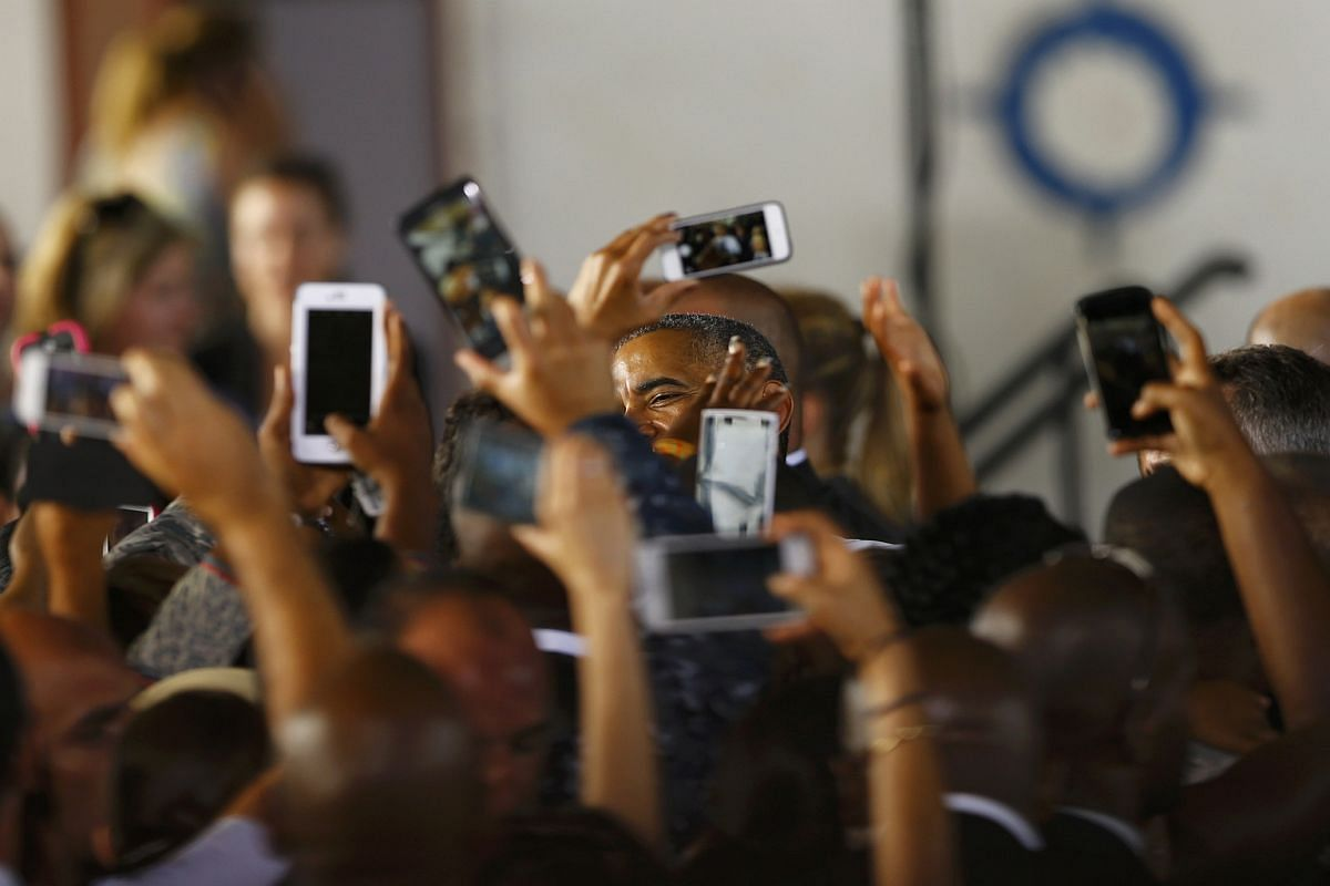 People take pictures of US President Barack Obama after his speech to army service members and their families at the Rota naval airbase, near Cadiz, Spain, on July 10.
