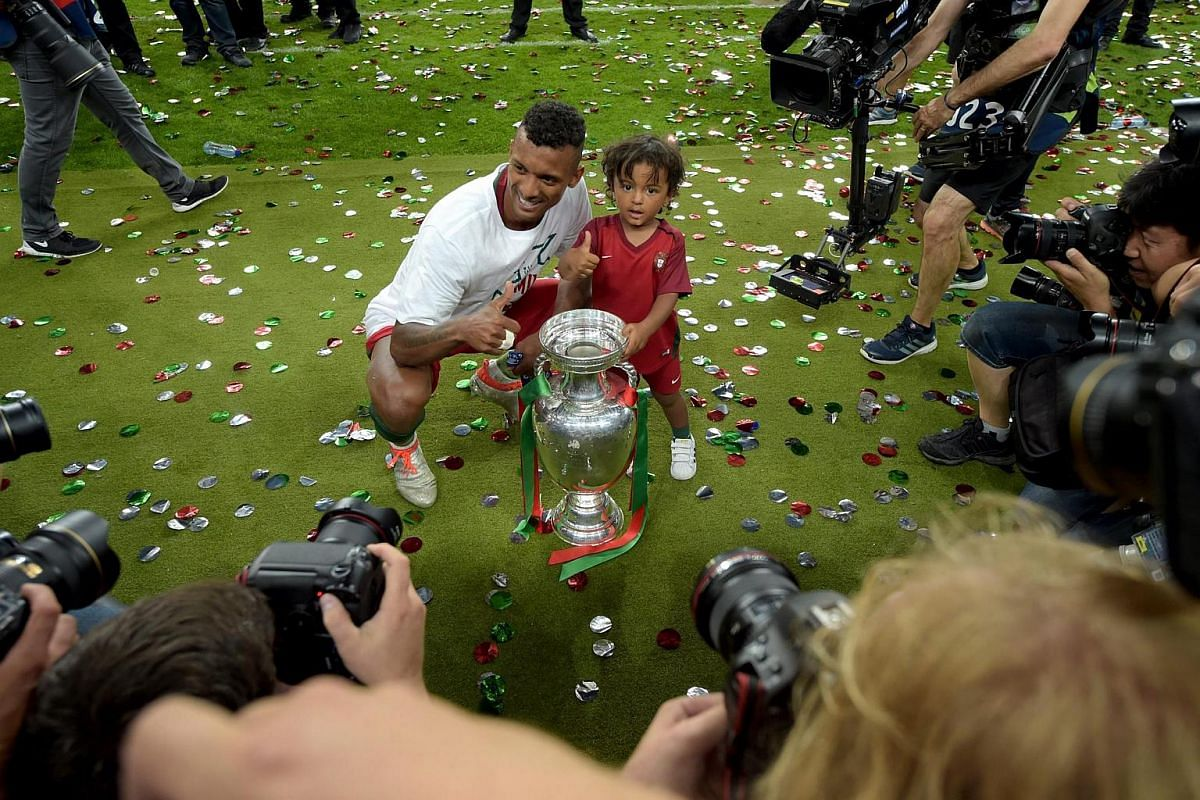 Nani of Portugal with his son pose for a picture with the trophy after winning the Euro 2016.