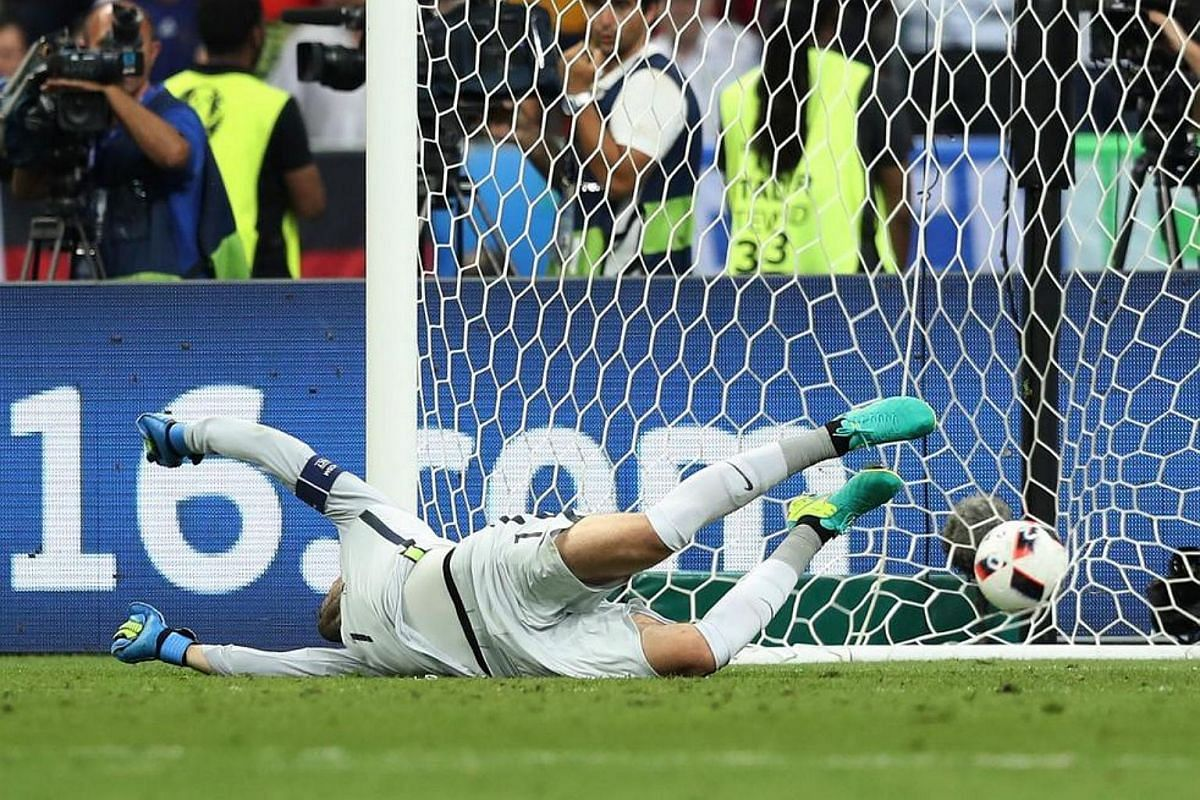 France's goalkeeper Hugo Lloris fails to stop the ball during the Euro 2016 final football match between Portugal and France.