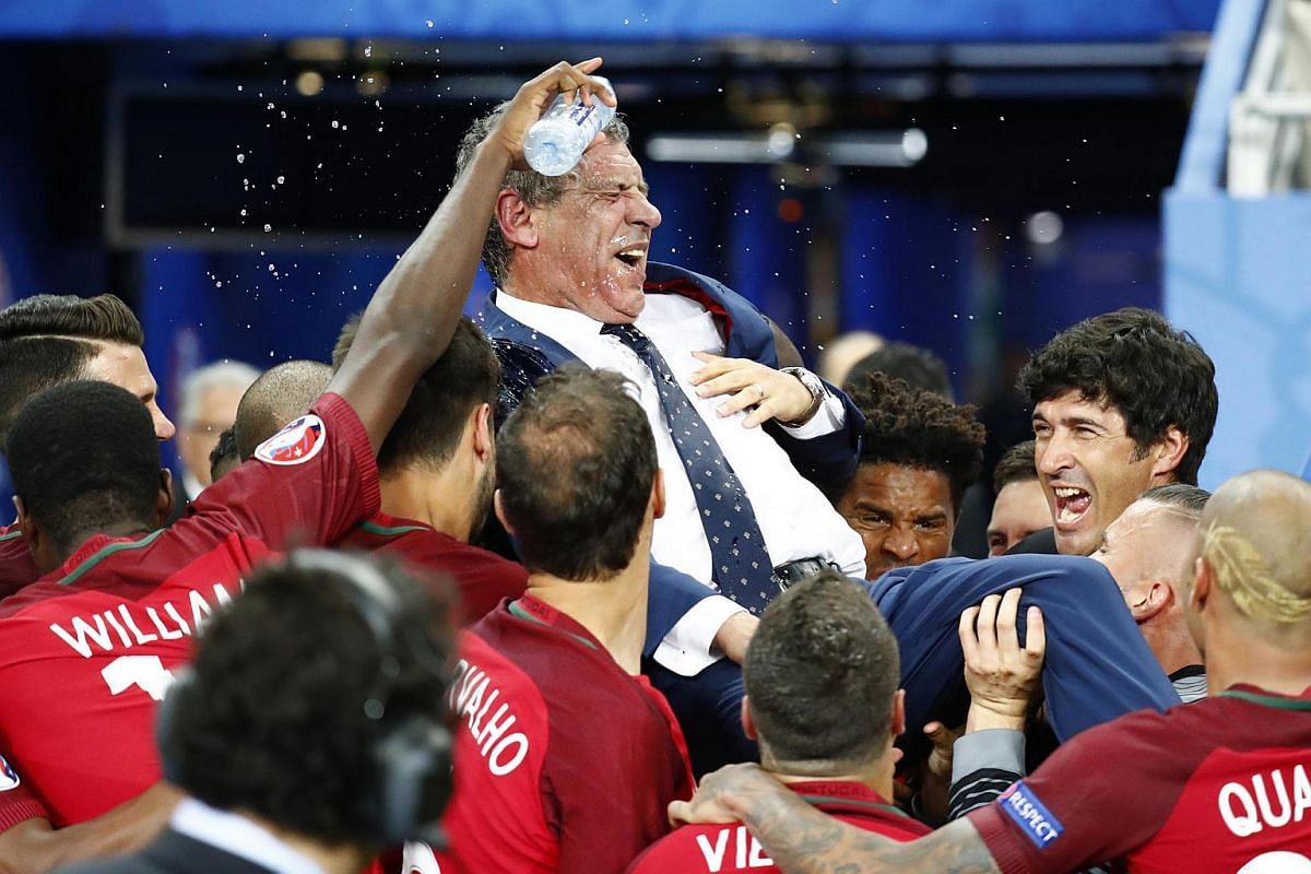 Portugal head coach Fernando Santos is lifted up by his players after winning the Euro 2016.