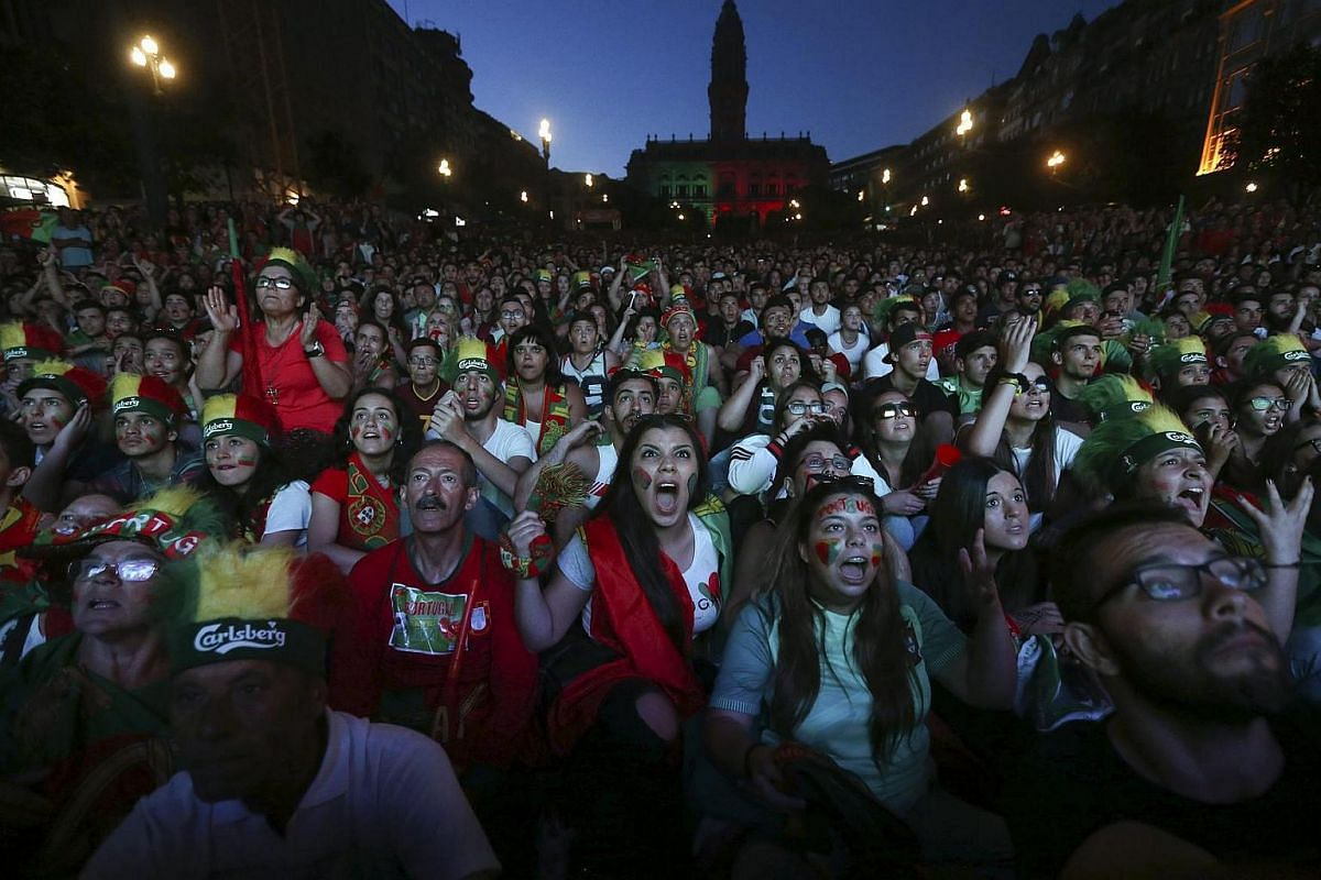 Supporters of Portugal react while watching the Euro 2016 final football match between Portugal and France.