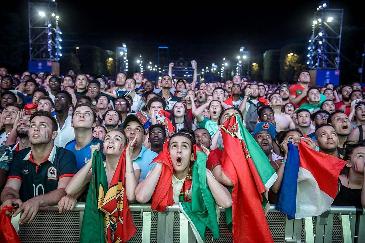 Portuguese and French fans react while watching the Euro 2016 final football match between Portugal and France.