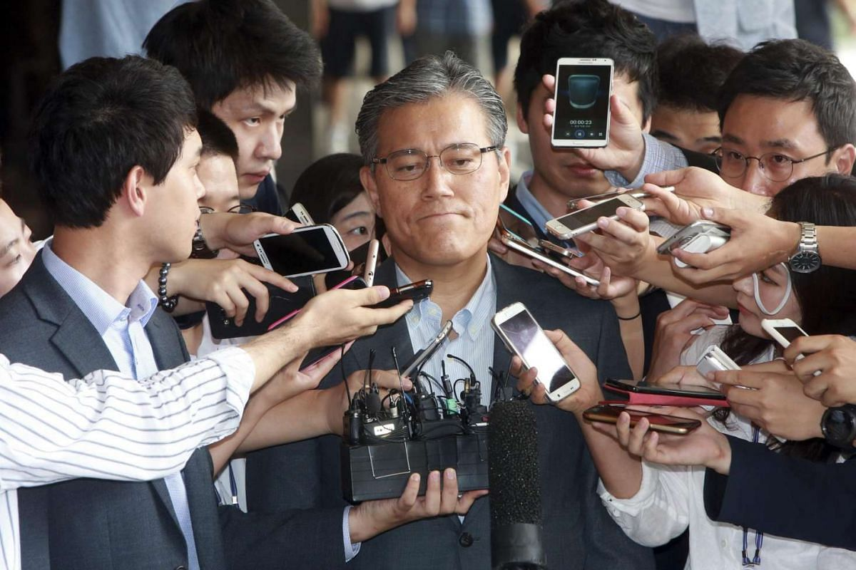 Kang Hyeon-gu (centre), chief of Lotte Homeshopping reacts during a press conference before appearing at the Seoul Central District Prosecutors' Office in southern Seoul, South Korea, on July 12, to undergo questioning over irregularities the company