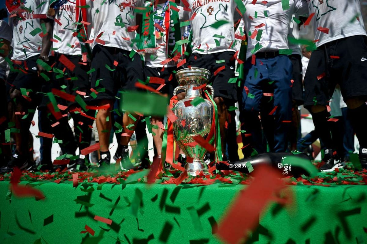 Portugal's football team players jump and sing next tto the trophy displayed on a stage at Alameda square in Lisbon on July 11 where thousands of supporters welcome them with scarfs and flags to celebrate their victory over France in their Euro 2016