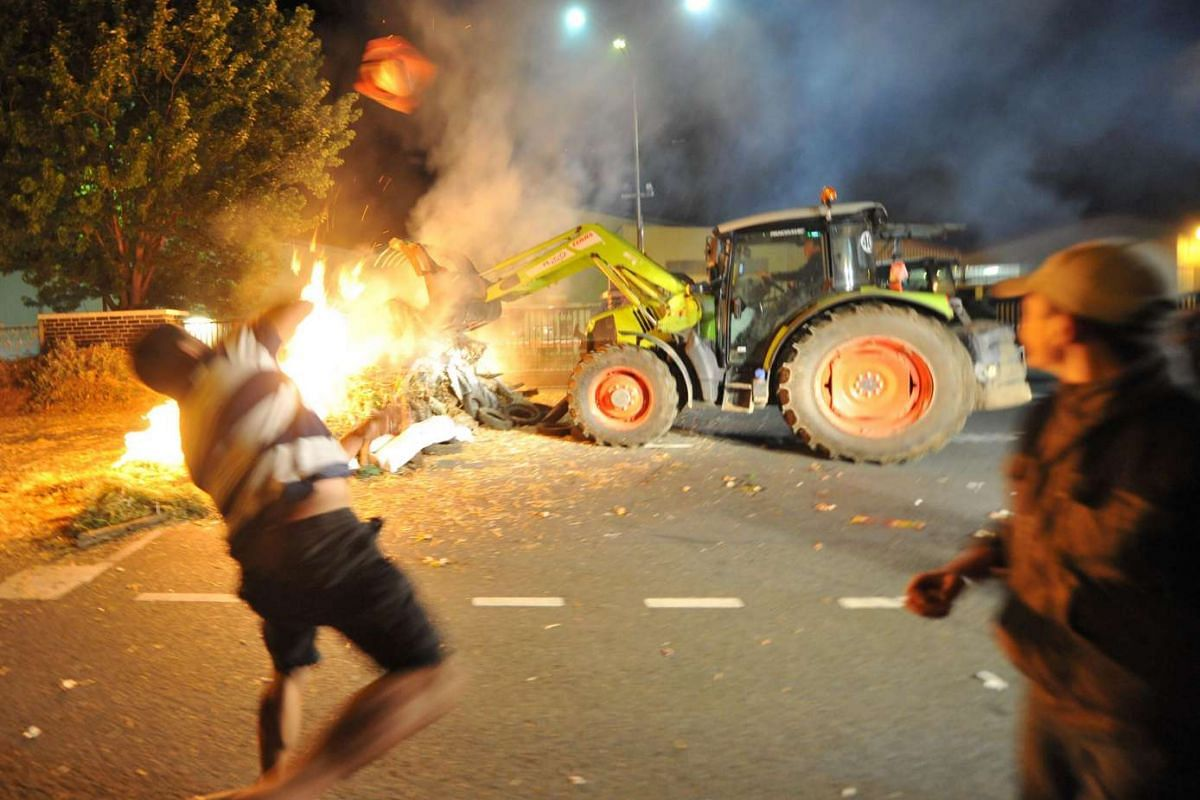 Protesters throw eggs and block access to SODIAAL, a dairy cooperative, to protest against the plunging prices of milk on July 12, in Le Mans, western France.
