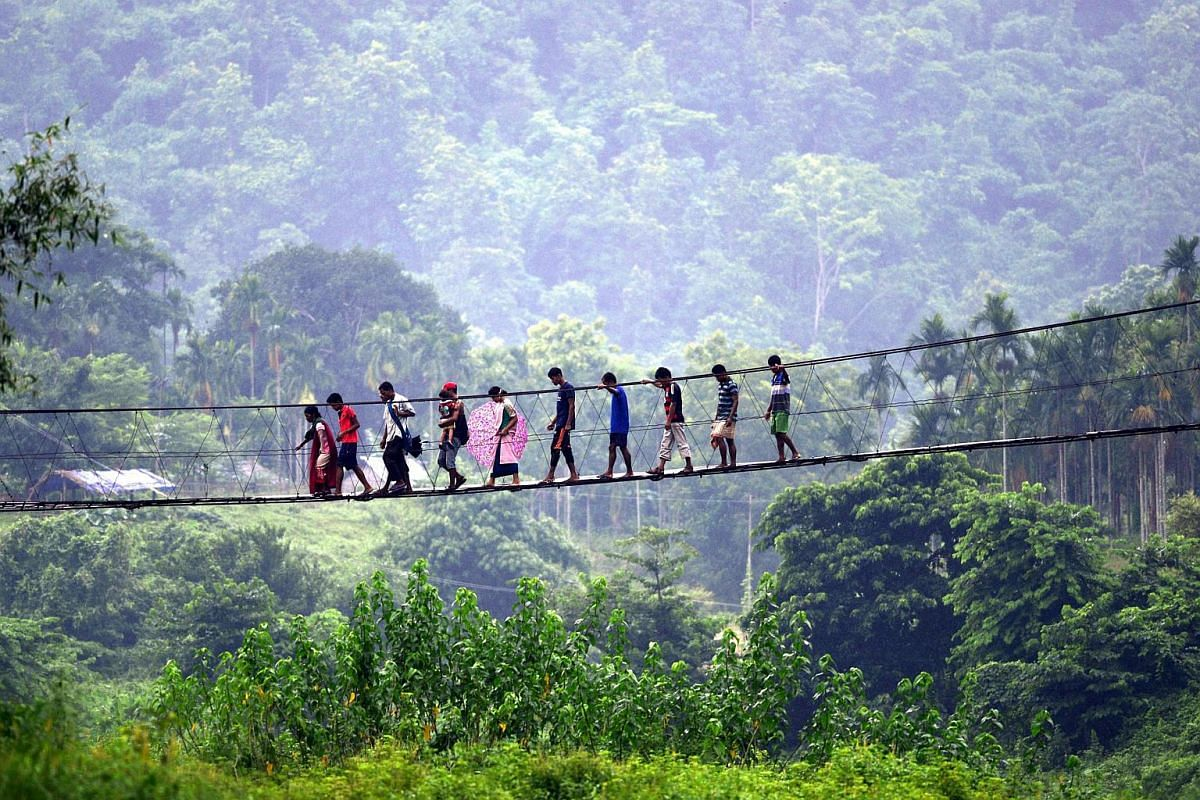 Villagers from Meghalaya state cross a bridge over the Shree river to buy goods from Ukiam weekly market in South Kamrup district of Assam state, India, on July 11.