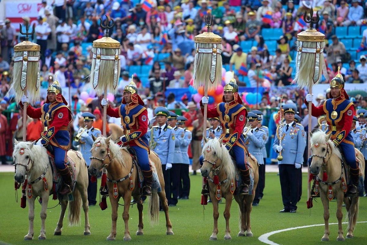 "Honour guards in uniforms ride on horseback carrying the ""Yesun Hult Tsagaan Tug"" (The Nine White Banners) arrive at the Central Stadium during the opening ceremony of the Naadam Festival in Ulaanbaatar, Mongolia on July 12, 2016."
