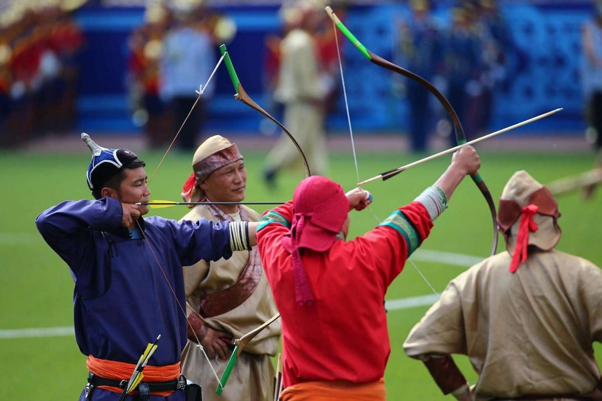Mongolians perform archery during the opening ceremony of the Naadam Festival in Ulaanbaatar, Mongolia on July 12, 2016.