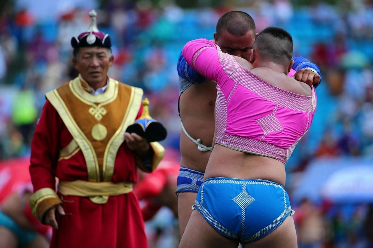 Mongolian wrestling competitors in action at the wrestling tournament during the opening ceremony of the Naadam Festival in Ulaanbaatar, Mongolia on July 12, 2016.
