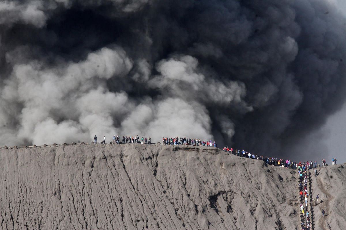 People standing on the edge of the crater while watching the eruption of Mount Bromo in Probolinggo, Indonesia on July 12, 2016.