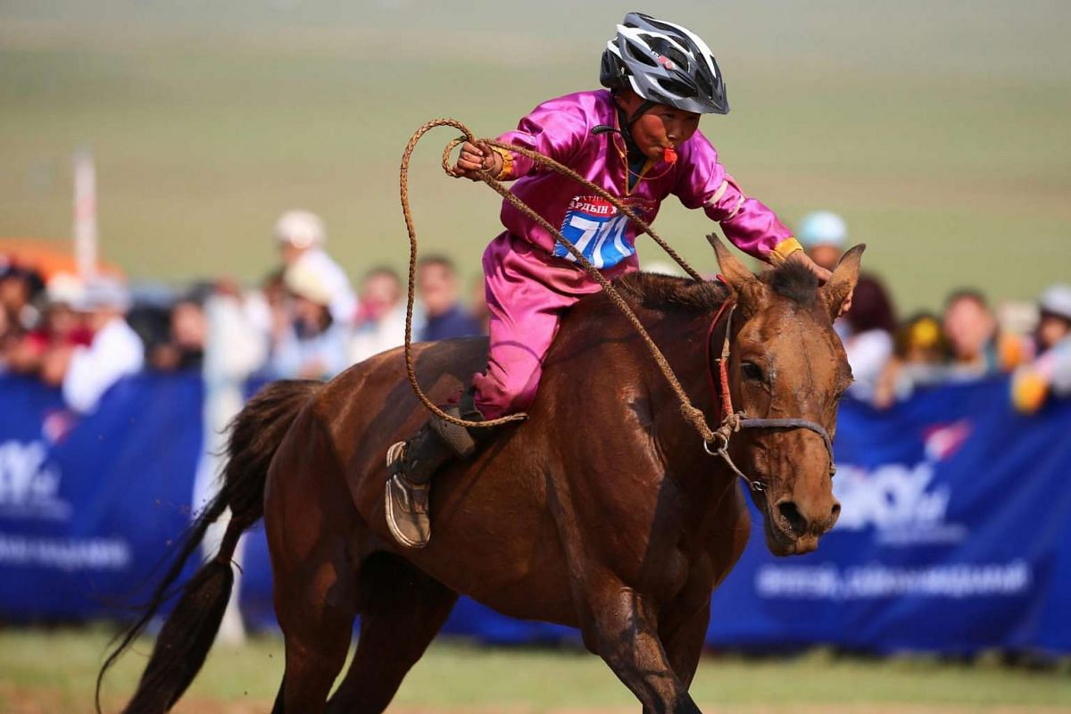 "A Mongolian child competes in the ""Soyolon"" (five-year-old horse) horse racing competition during Naadam Festival in Ulaanbaatar, the capital of Mongolia on July 12, 2016."