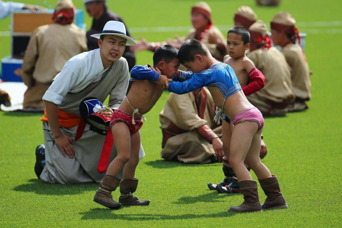 Mongolian children in traditional attire wrestle during the opening ceremony of the Naadam Festival in Ulan Bator, Mongolia on July 12, 2016.