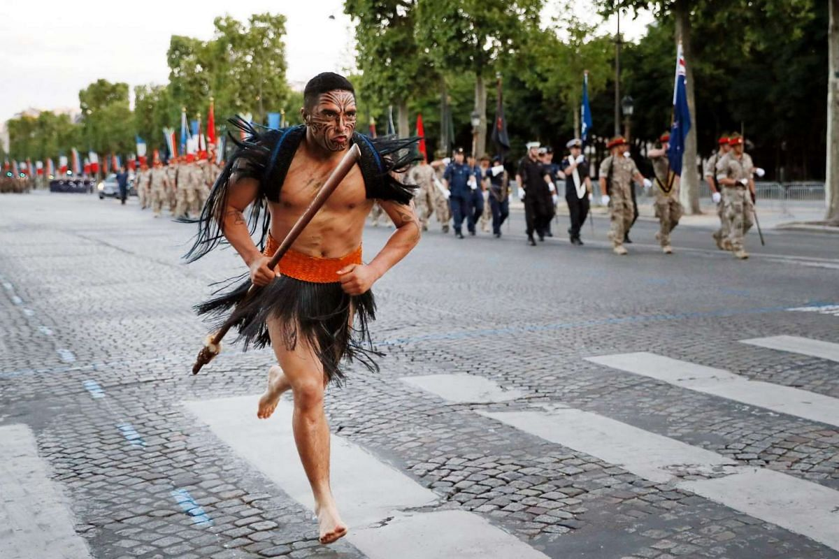 A Maori soldier runs as New Zealand's soldiers march down the Champs Elysees in Paris during a rehearsal of the annual Bastille Day military parade on July 12, 2016.