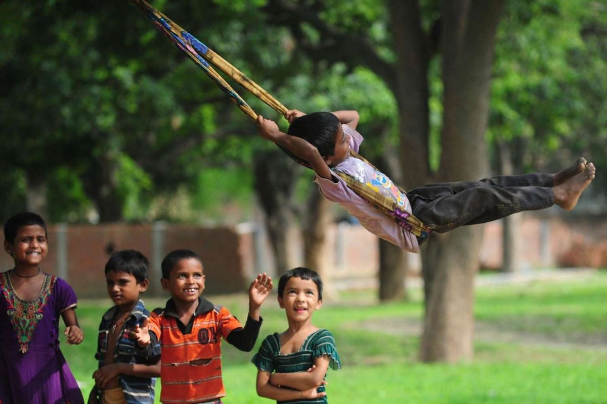 Indian children play on a swing in a village on the outskirts of Allahabad on July 12, 2016.