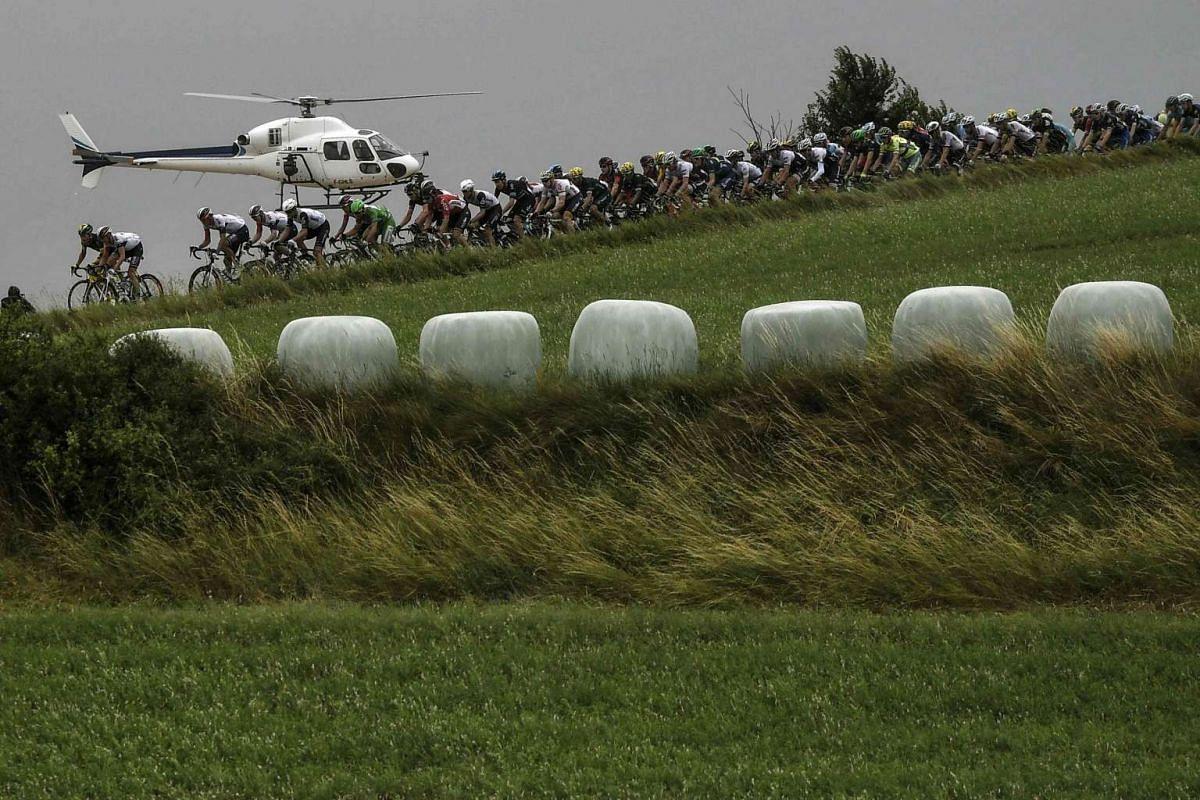 The pack ride near an helicopter during the 197 km tenth stage of the 103rd edition of the Tour de France cycling race on July 12, 2016 between Escaldes-Engordany and Revel.