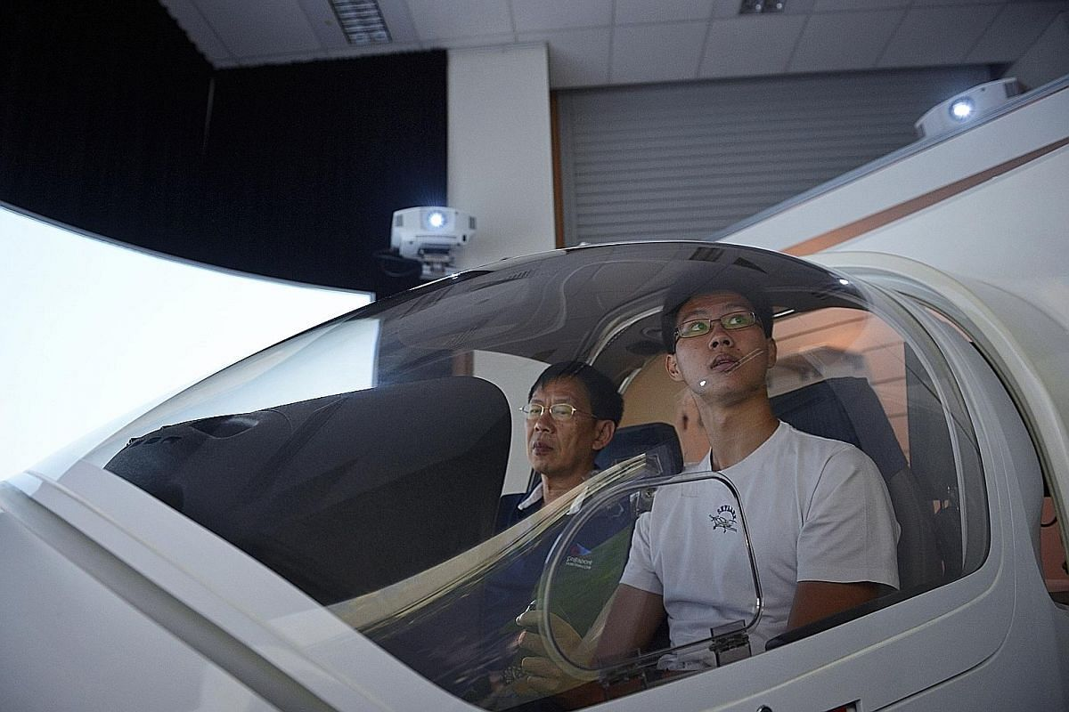 Ryan Lee, 18, a student from Anderson Junior College, undergoing flight simulator training just days prior to his test for his Private Pilot Licence at the club. He is guided by flight simulator instructor Seah Ser Liang, 61. Temasek Polytechnic stud