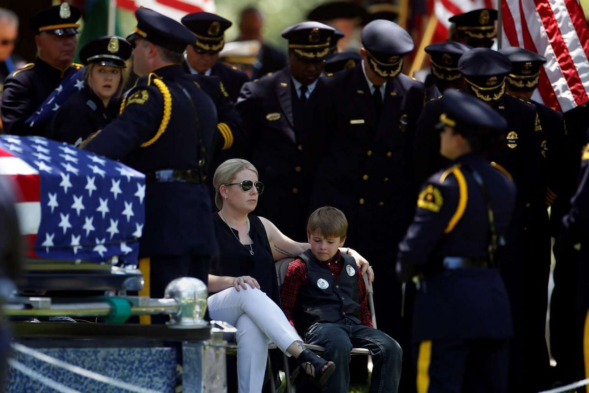 Katrina Aherns sits with her son Magnus Aherns during the funeral of her husband, slain Dallas police officer Lorne Ahrens, following the multiple police shootings in Dallas, Texas, on July 13, 2016.