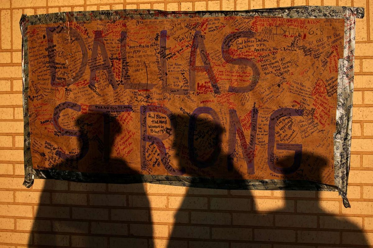 The shadows of three officers are cast on a Dallas Strong sign at a makeshift memorial at police headquarters following the multiple police shootings in Dallas, Texas, on July 13, 2016.