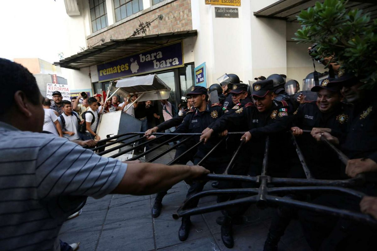 Teachers pull at barricades used by policemen to block access to a commercial area during a protest against President Enrique Pena Nieto's education reform, in Monterrey, Mexico, on July 13, 2016.