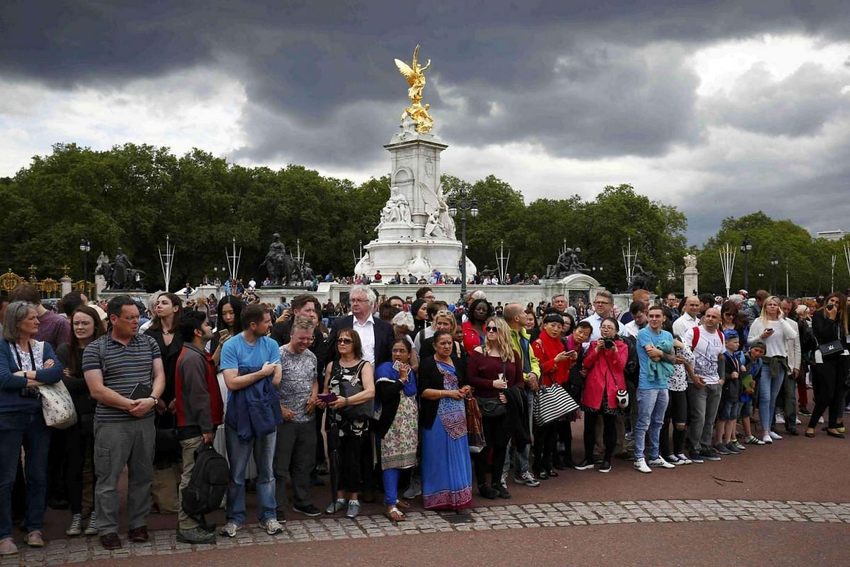 Onlookers wait outside Buckingham Palace for the arrival of outgoing Prime Minister David Cameron and incoming prime minister Theresa May in central London on July 13.