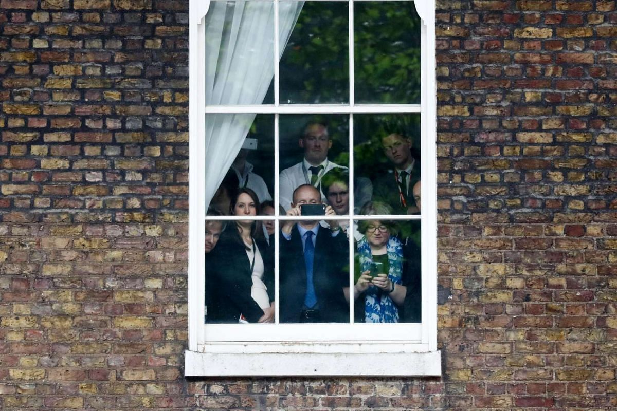 Downing Street staff look out from a window as incoming British Prime Minister Theresa May speaks.