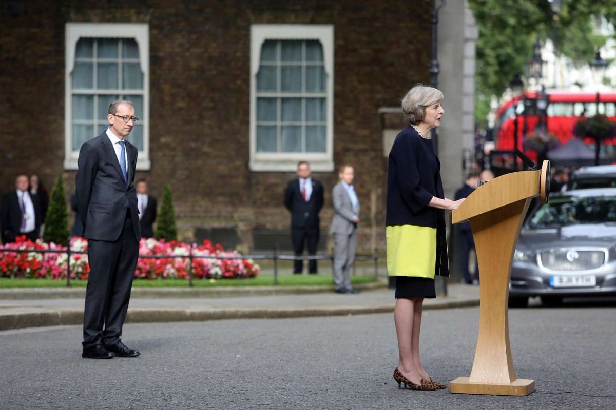 British Prime Minister Theresa May speaks as her husband Philip looks on in Downing Street in London.