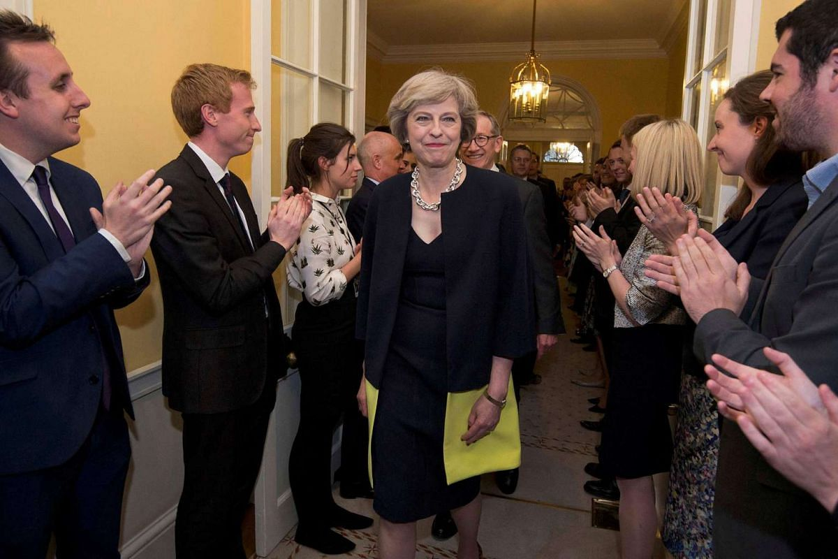 Staff applaud as Britain's new Prime Minister Theresa May and her husband walk into 10 Downing Street.