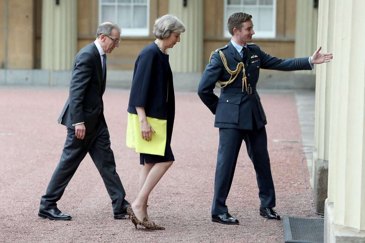 Mrs Theresa May followed by her husband Philip arrives at Buckingham Palace to meet Queen Elizabeth II.