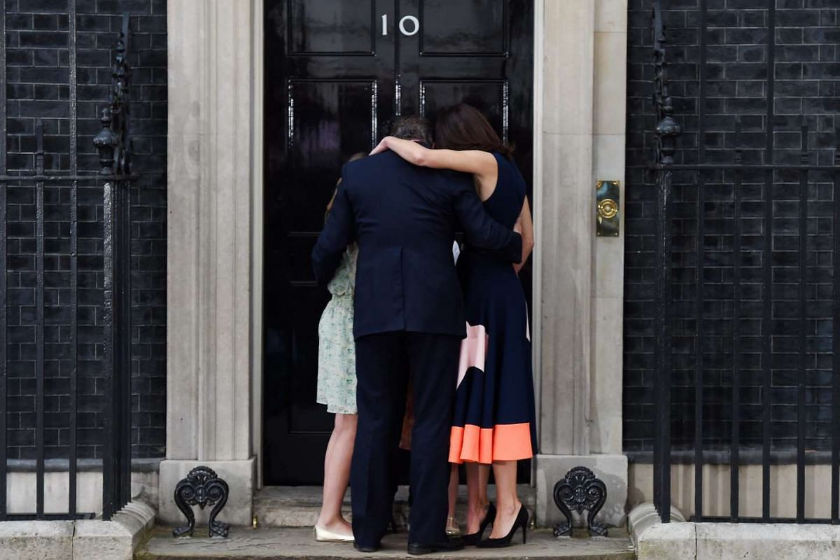 The Cameron family share a hug outside the door of the place they called home for the past six years.
