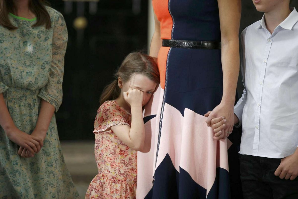 Mr David Cameron's young daughter Florence wipes a tear from her eye as the family bid farewell to their residence of six years.