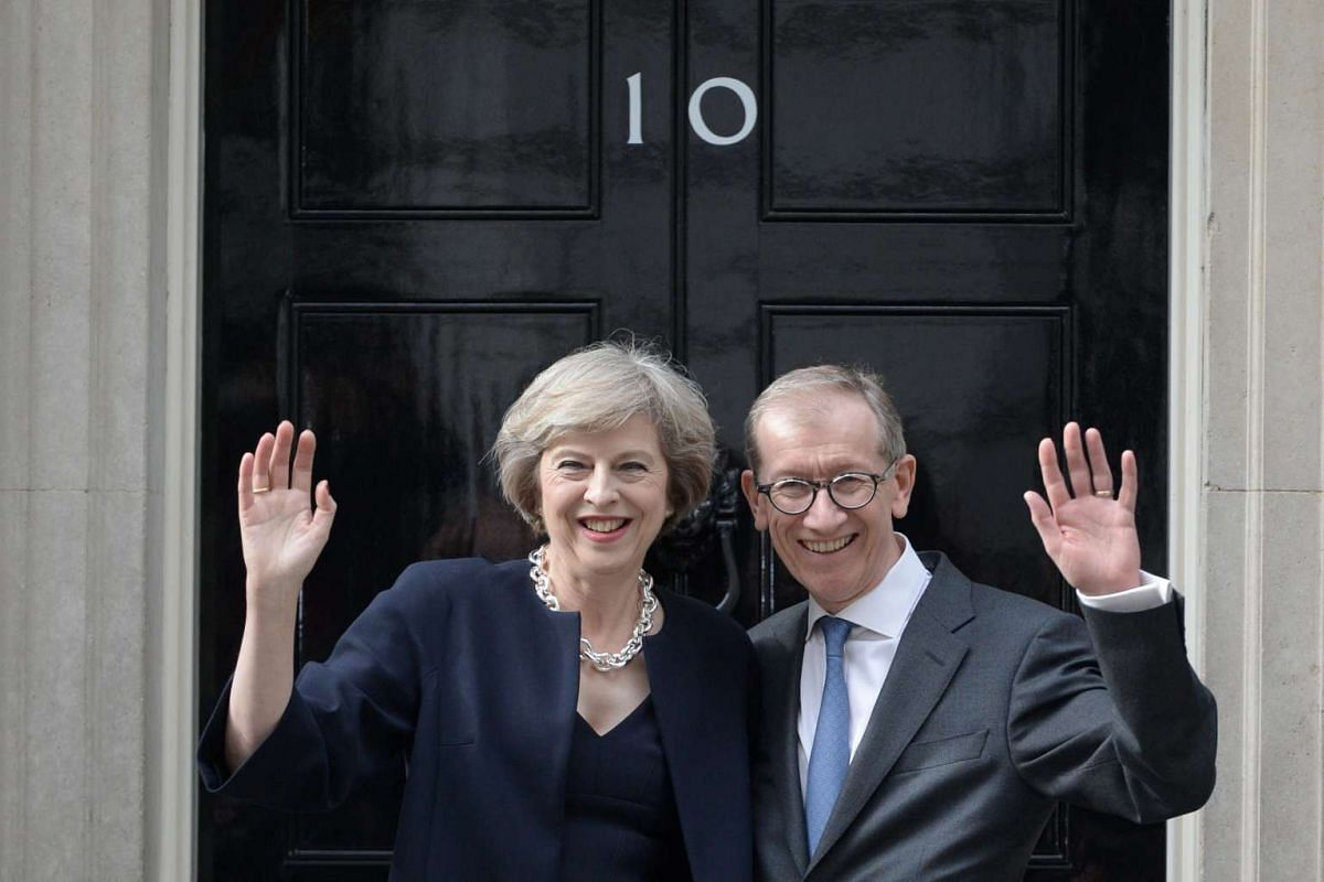 Britain's Prime Minister Theresa May and husband Philip waving to the crowd outside 10 Downing Street before entering as its new residents.