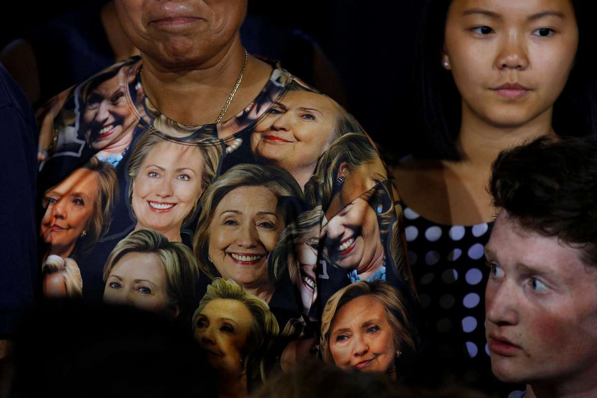 A woman wears a t-shirt with pictures of US Democratic Presidential candidate Hillary Clinton ata campaign rally at Ernst Community Cultural Centre in Annandale, Virginia, on July 14, 2016.