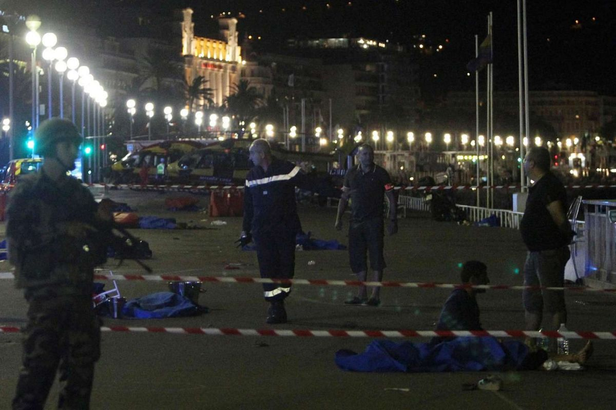 Soldiers, police officers and firefighters walk near dead bodies covered with blue sheets on the Promenade des Anglais seafront in Nice, France, on July 15, 2016.