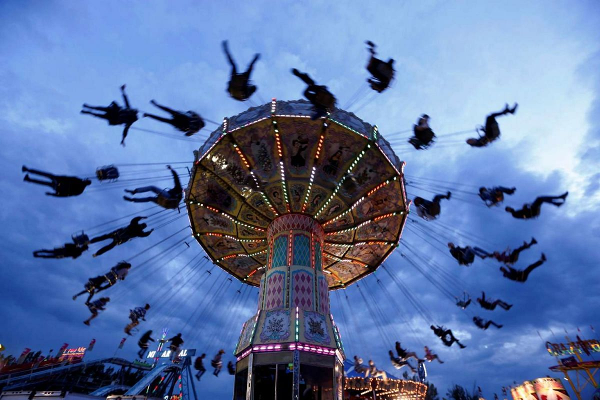 People swing on a ride during the Calgary Stampede in Calgary, Alberta, Canada, on  July 14, 2016.
