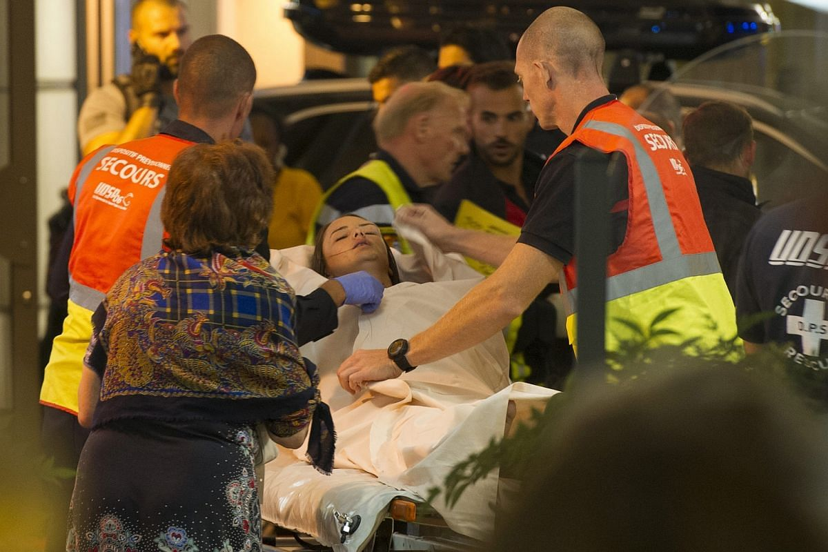 An emergency team assists the wounded and evacuates them from the scene where a truck crashed into the crowd.